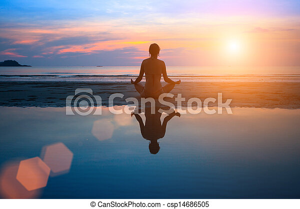 Silhouette young woman practicing yoga on the beach at sunset - csp14686505