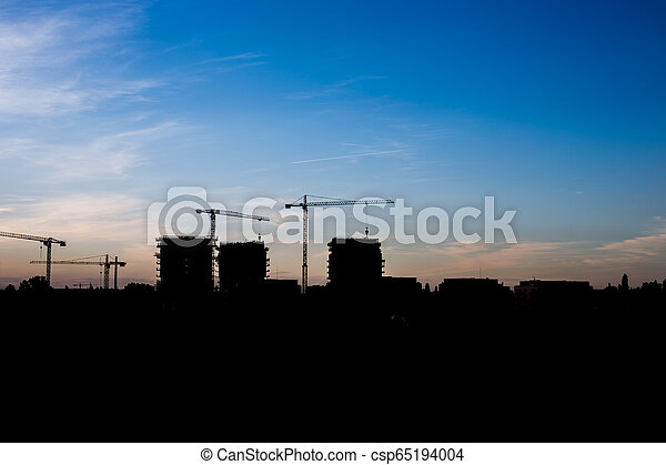 Silhouettes high-rise buildings under construction on background of the blue sky - csp65194004