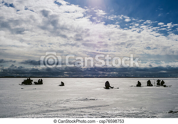 silhouettes of fishermen fishing and snowmobile in winter on the ice - csp76598753