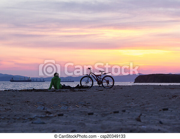 Silhouettes of people on the beach at sunset - csp20349133