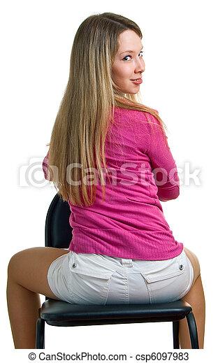 La chica sonriente se sienta en una silla - csp6097983