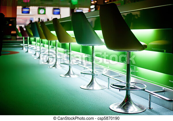 Sillas en el bar con luces verdes - csp5870190