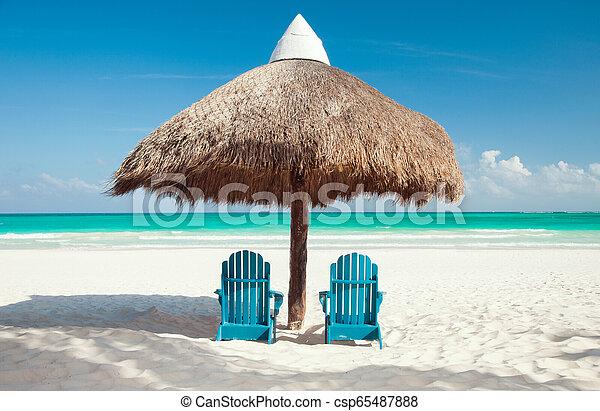 Dos sillas solares bajo el palapa en la playa tropical - csp65487888