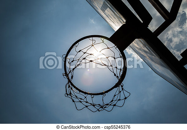 Siluate basketball hoop under the sun and blue sky - csp55245376