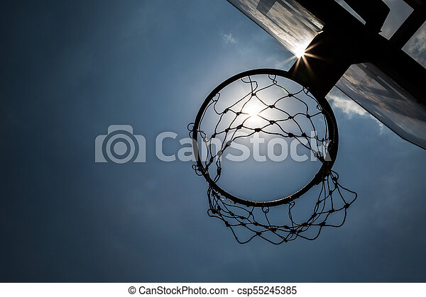 Siluate basketball hoop under the sun and blue sky - csp55245385