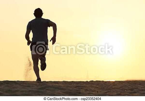 Silueta de un corredor corriendo por la playa - csp23352404