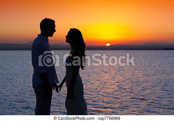 Una pareja enamorada de la silueta de la luz del lago Sunset - csp7756969