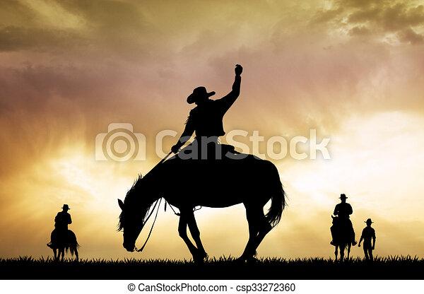 Silueta de vaquero rodeo al atardecer - csp33272360
