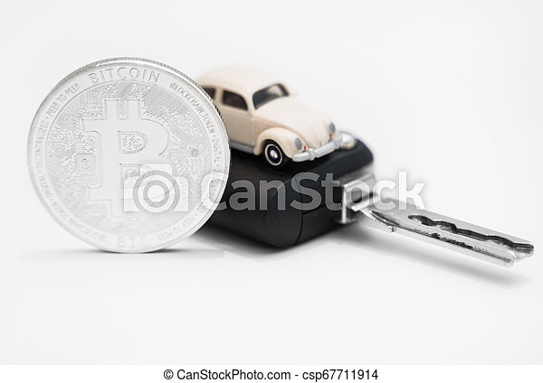 Silver physical bitcoin and car key on white background. - csp67711914