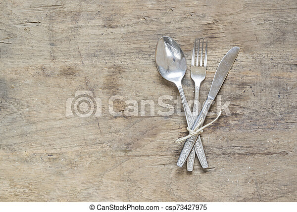 Silver spoon, fork and knife on old, rusty, wooden background - csp73427975