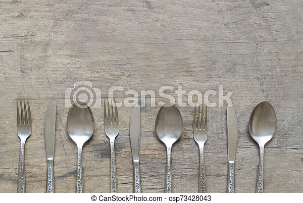 Silver spoons, forks and knives on old, rusty, wooden background - csp73428043