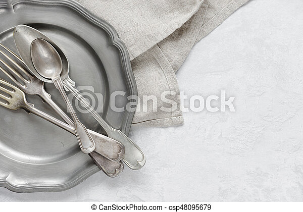 Silverware on a pewter plate - csp48095679