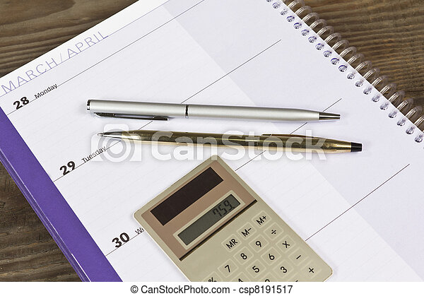 simple financial planner monthly calendar with two pens and small