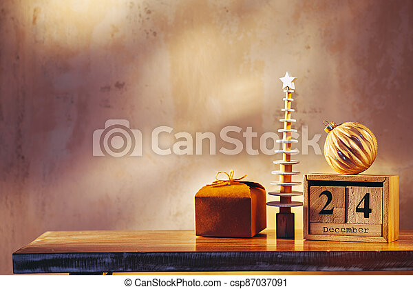 Simple image with christmas tree, gift, ornament and wooden calendar - csp87037091