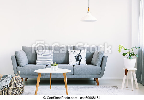 Pleasant Simple Interior Of A Bright Living Room With White Pillows On A Gray Sofa Next To A Stool With A Monstera Plant On It Real Photo Machost Co Dining Chair Design Ideas Machostcouk