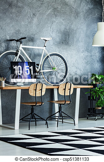 Two wooden chairs at table with computer monitor and bicycle in simple work area with geometric carpet