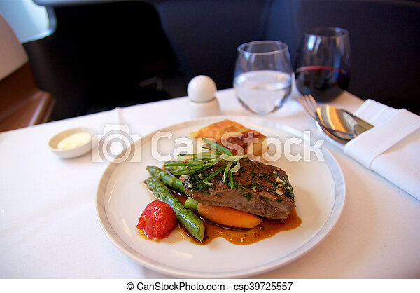 SINGAPORE - JULY 22, 2016: Business Class meal in a plane with red wine - csp39725557