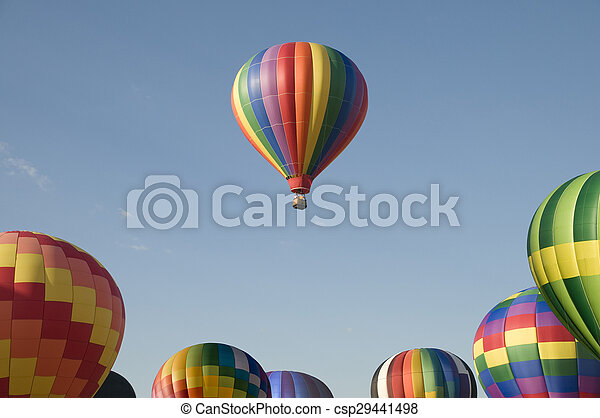 Single hot-air balloon floating above a balloon festival - csp29441498