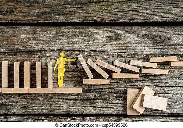 Single man holding up falling wooden bricks in a conceptual image