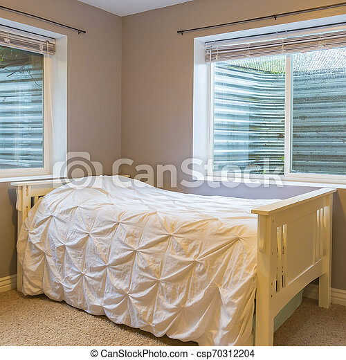 Single wooden bed with outside light shining in - csp70312204