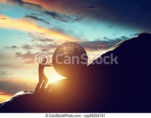 Sisyphus metaphor. Man rolling huge concrete ball up hill. - csp26254741