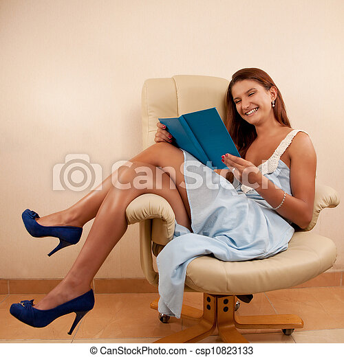 sitting in chair reading book - csp10823133