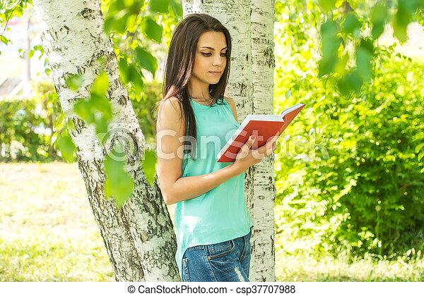 sitting in grass, reading book in summer sun light - csp37707988