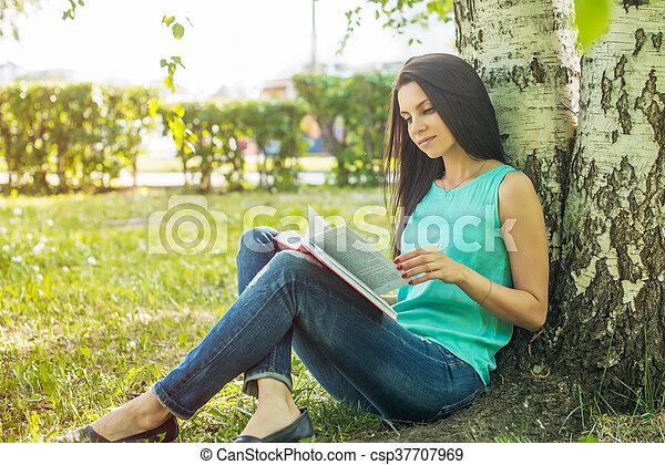 sitting in grass, reading book in summer sun light - csp37707969