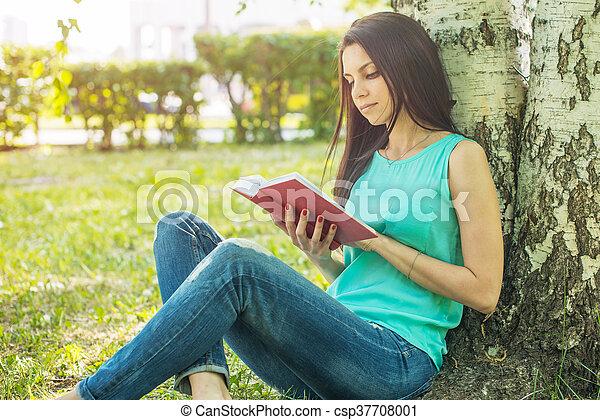 sitting in grass, reading book in summer sun light - csp37708001