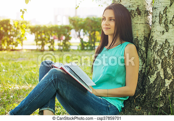sitting in grass, reading book in summer sun light - csp37859701