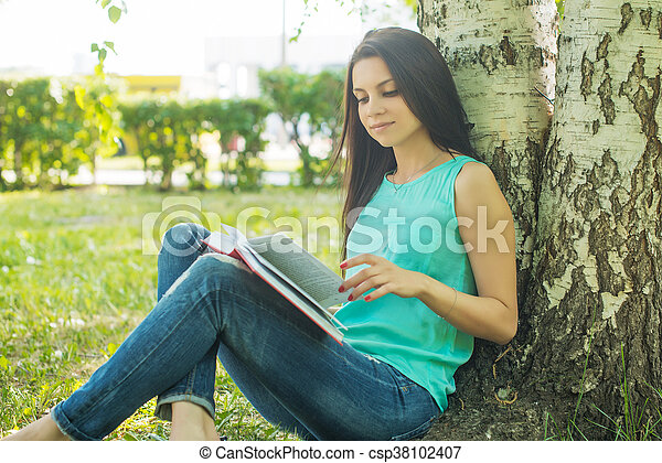 sitting in grass, reading book in summer sun light - csp38102407