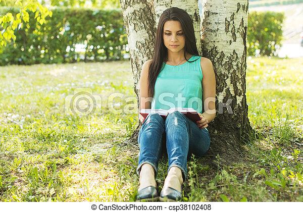 sitting in grass, reading book in summer sun light - csp38102408