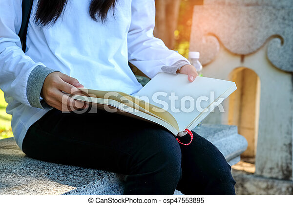 sitting on a chair reading a book. - csp47553895