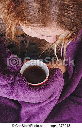 sitting on sofa in livingroom with tea - csp41373918