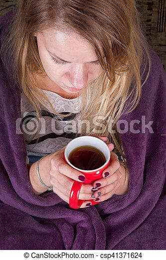 sitting on sofa in livingroom with tea - csp41371624