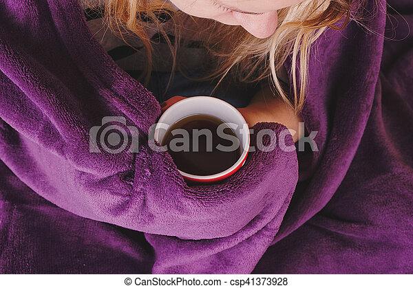 sitting on sofa in livingroom with tea - csp41373928