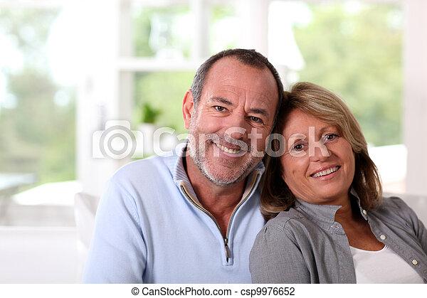 Portrait eines glücklichen Senior Paares, das auf dem Sofa sitzt - csp9976652