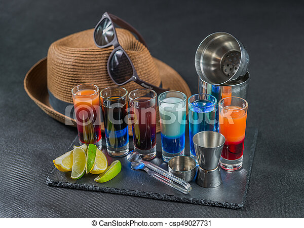 Six Different Colored Shot Drinks Lined Up On A Black Stone Plate