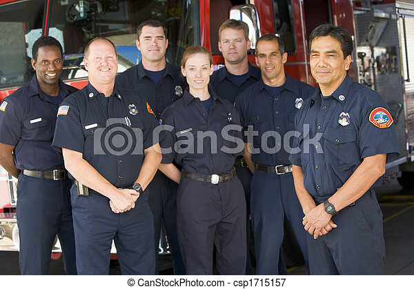 Six firefighters standing in front of fire engine with captain (depth of field) - csp1715157