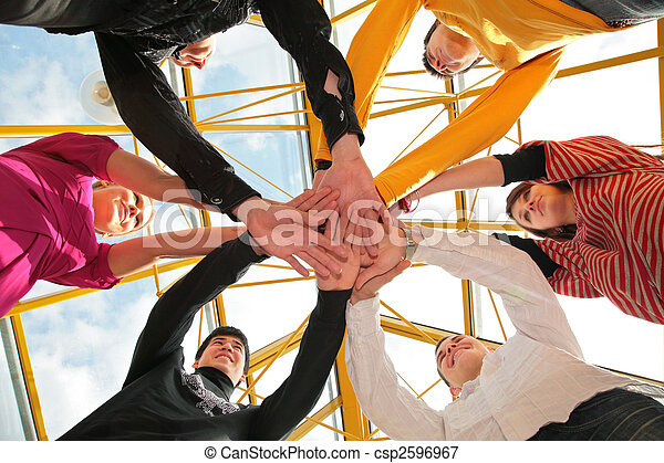 Six friends joining hands low angle view - csp2596967
