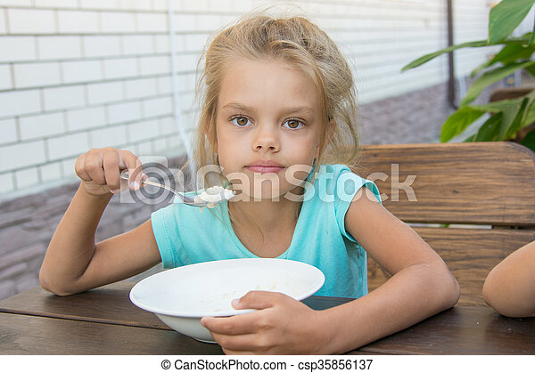 Six year old girl at a wooden table in the yard eating porridge - csp35856137