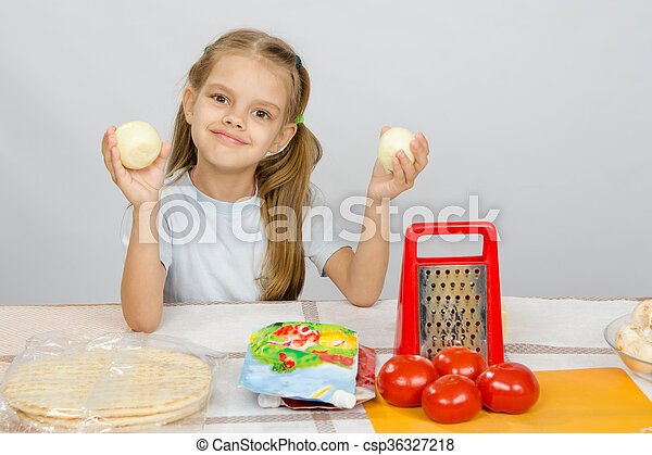 Six year old girl at the kitchen table having fun holding vegetables - csp36327218