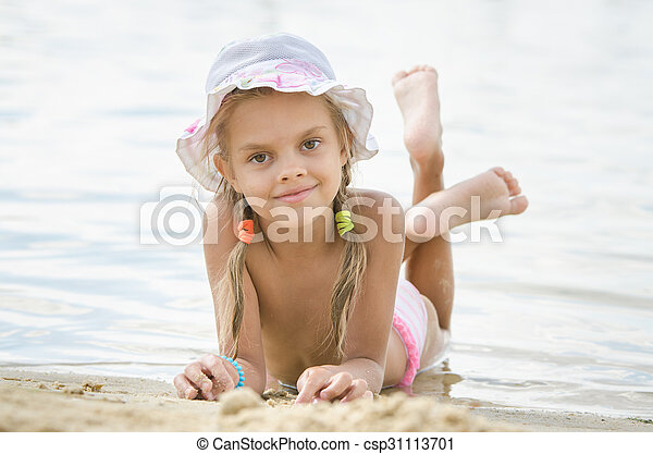 Six year old girl lying on the sand on the beach - csp31113701