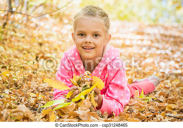 Six year old girl lying on the yellow fallen leaves - csp31248465