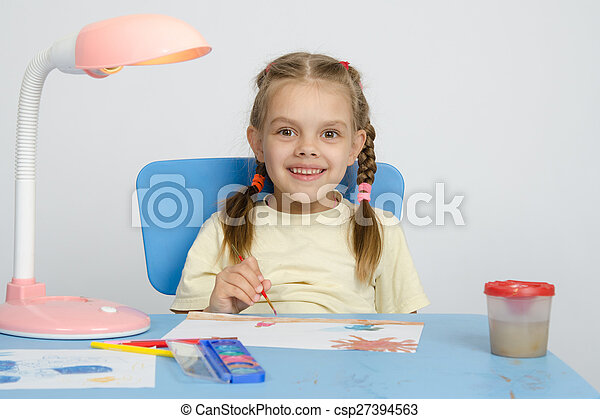 Six year old girl smiling happily, drawing the table - csp27394563