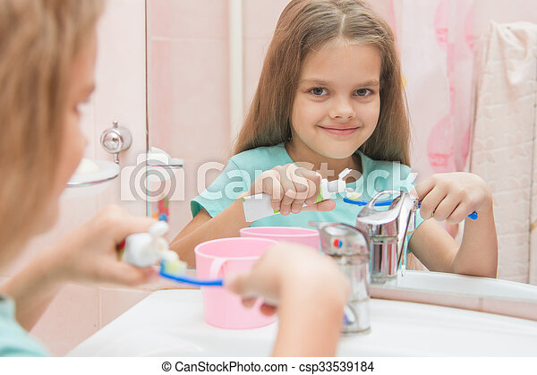 Six year old girl squeezes the toothpaste from a tube on toothbrush - csp33539184