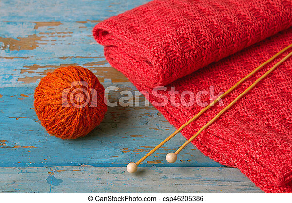 Skein of wool red knitted scarf and knitting needles - csp46205386