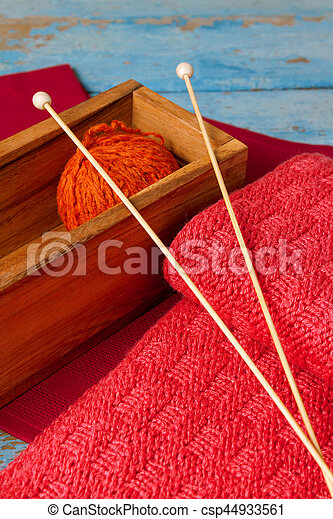 Skein of wool, spokes and a red knitted scarf - csp44933561