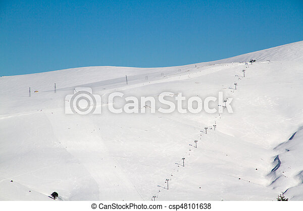 Ski tracks on the background of snowy mountains and blue sky - csp48101638