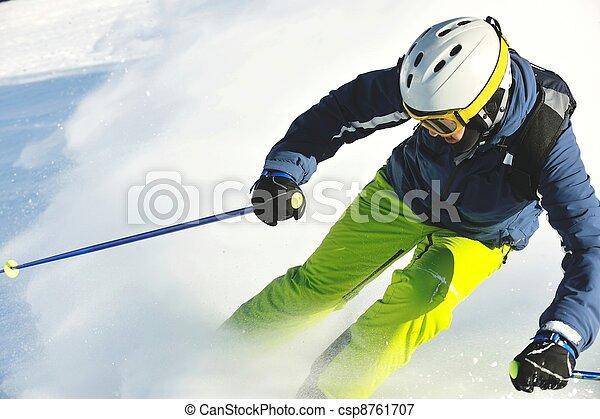 skiing on fresh snow at winter season at beautiful sunny day - csp8761707